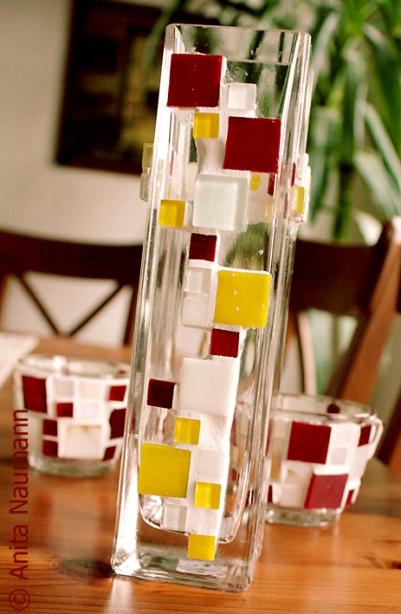 Kombination aus viereckiger Vase und Kerzengläsern in Rot, Gelb und Weiß